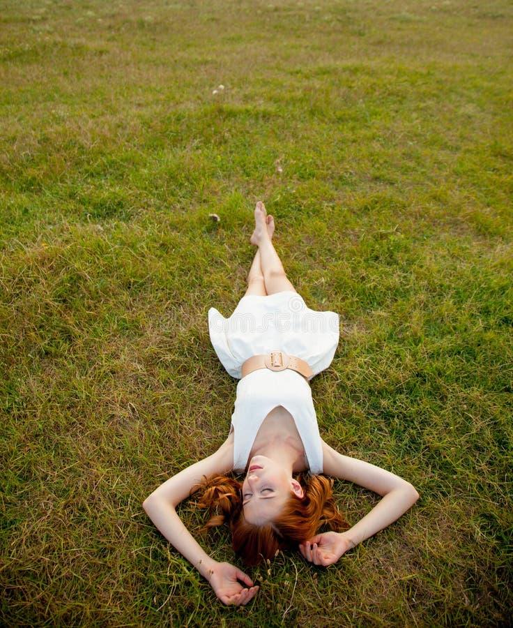 härlig ung kvinna som ligger i fältet och koppla av arkivfoton
