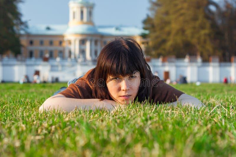 Härlig ung kvinna som ligger på ett fält, grönt gräs Tyck om utomhus naturen arkivbild