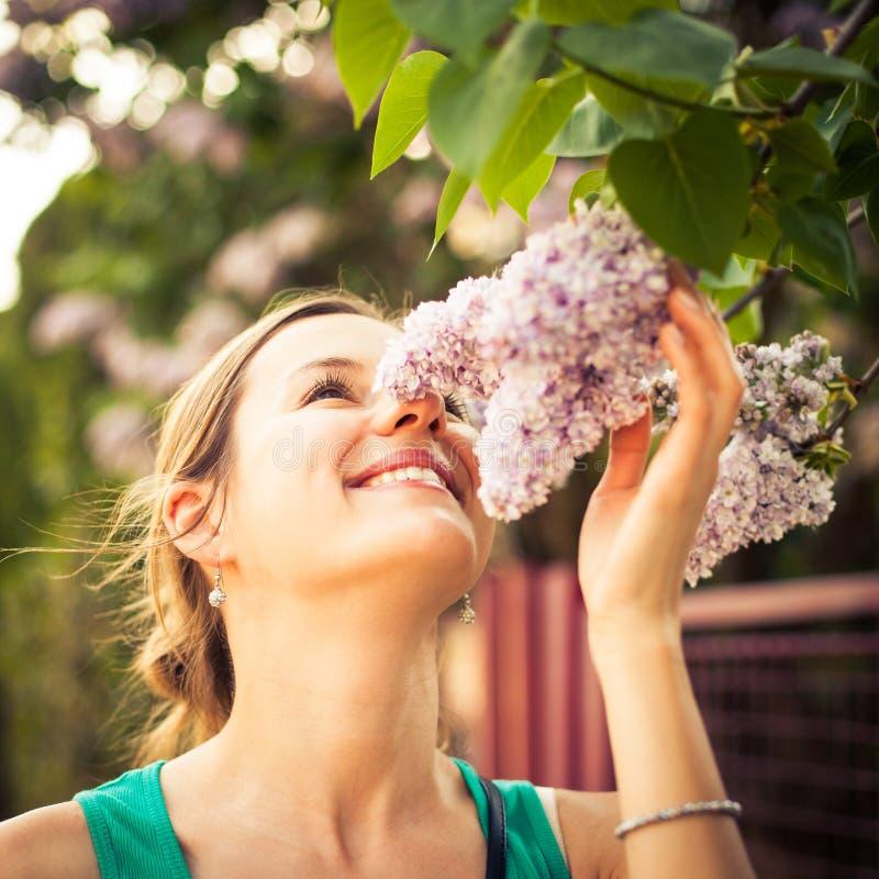 Härlig ung kvinna som luktar jasminblommor arkivbilder