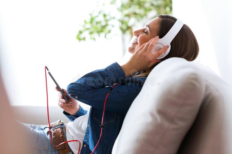 Härlig ung kvinna som lyssnar till musik med den hemmastadda mobiltelefonen royaltyfri bild