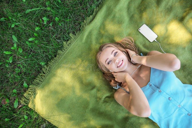 Härlig ung kvinna som lyssnar till musik, medan ligga på grönt gräs utomhus arkivbild