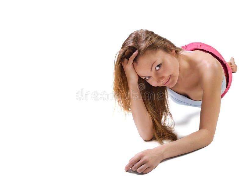 Härlig ung kvinna som ner ligger golvet arkivbild