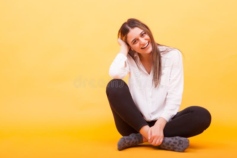 Härlig ung kvinna som ner sitter och ler över gul bakgrund royaltyfri foto