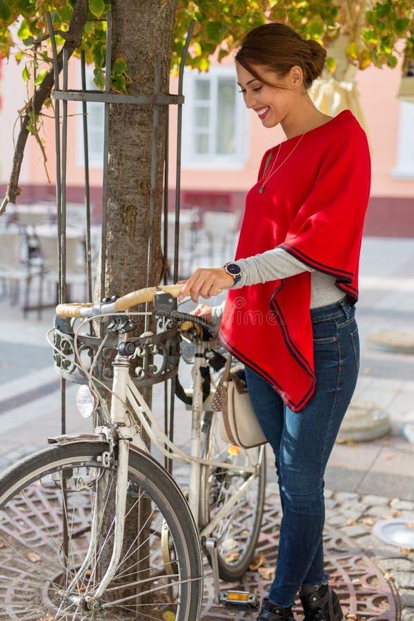 Härlig ung kvinna som parkerar hennes cykel bredvid ett träd arkivbilder