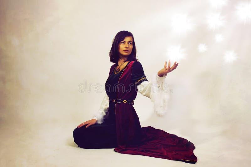 Härlig ung kvinna som poserar i den historiska klänningen som gör en dramatisk gest royaltyfri fotografi