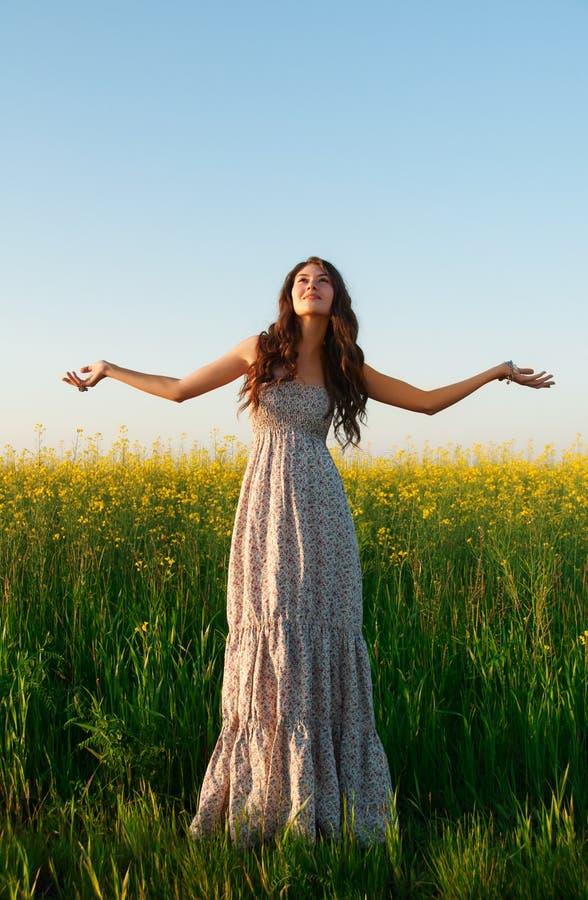Härlig ung kvinna som poserar i rapsfröfältet fotografering för bildbyråer