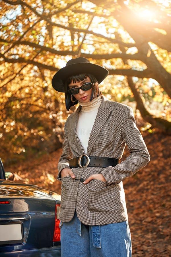 Härlig ung kvinna som poserar nära cabrioleten säsong för bana för höstfallskog arkivbilder