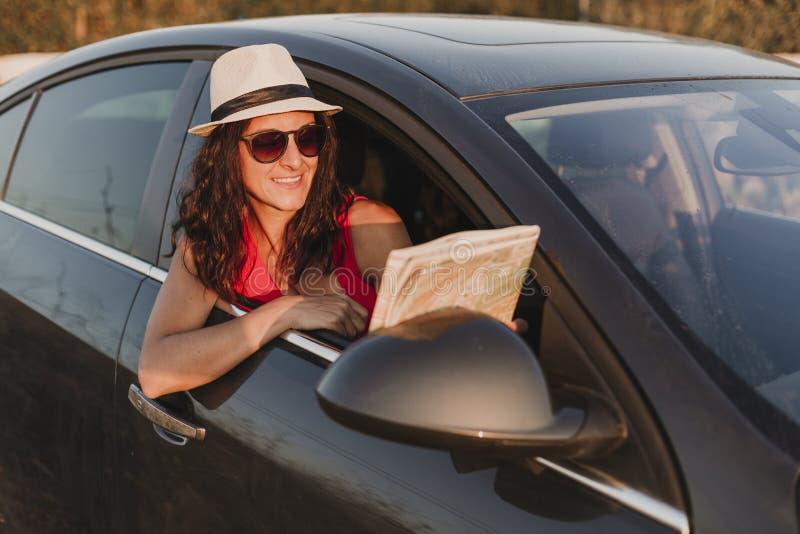 Härlig ung kvinna som reser i en bil och rymmer en översikt Lopp- och gyckelbegrepp Solnedgång och livsstil royaltyfri bild