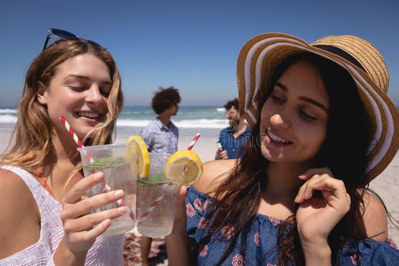 Härlig ung kvinna som rostar coctailexponeringsglas på stranden i solskenet arkivbild