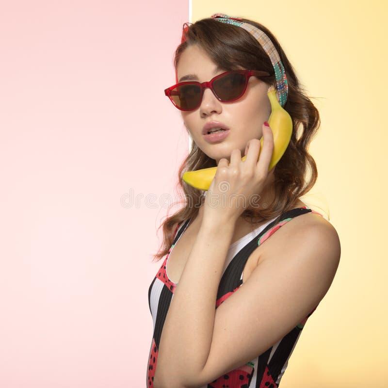 Härlig ung kvinna som rymmer en banan nära örat Kvinna i exponeringsglas på en kulör bakgrund Popkonst arkivfoton