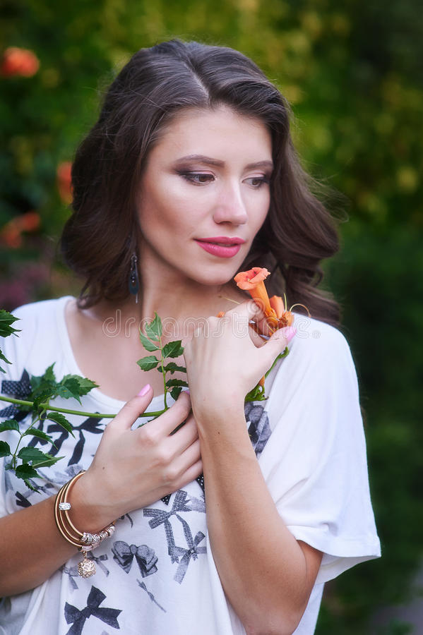 Härlig ung kvinna som rymmer en blomma royaltyfri foto