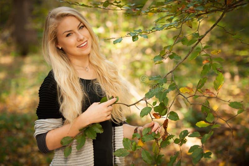Härlig ung kvinna som rymmer en filial med gröna sidor i skogen arkivfoto
