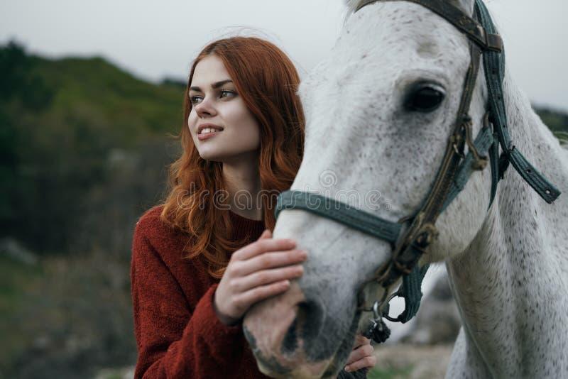 Härlig ung kvinna som rymmer en vit häst, stående, berg, natur royaltyfri foto