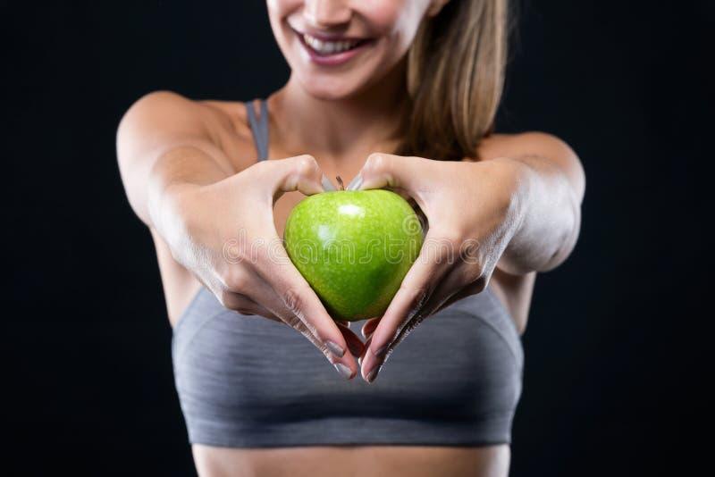 Härlig ung kvinna som rymmer ett äpple över svart bakgrund royaltyfria bilder