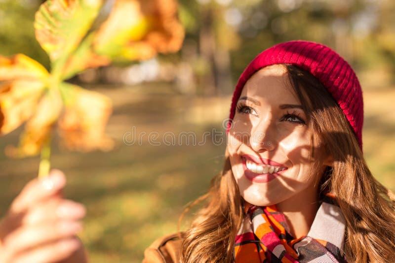 Härlig ung kvinna som rymmer ett höstblad in i solcreatien royaltyfria foton
