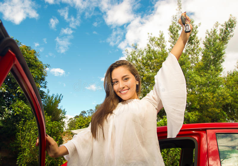 Härlig ung kvinna som rymmer henne tangenter och nära ler av hennes öppna röda bil arkivbilder