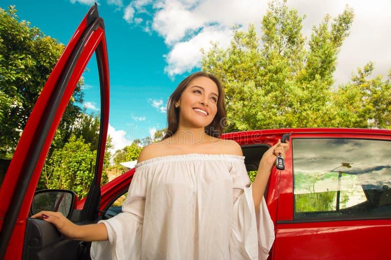 Härlig ung kvinna som rymmer henne tangenter och nära ler till hennes egen röda bil arkivfoton