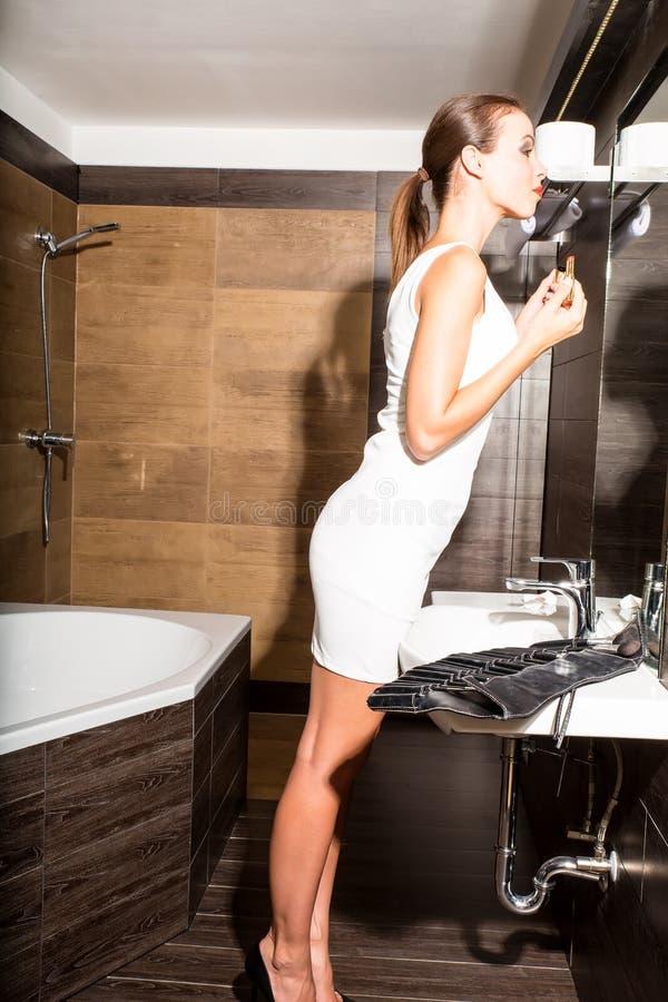 Härlig ung kvinna som sätter på makeup i badrummet royaltyfri bild