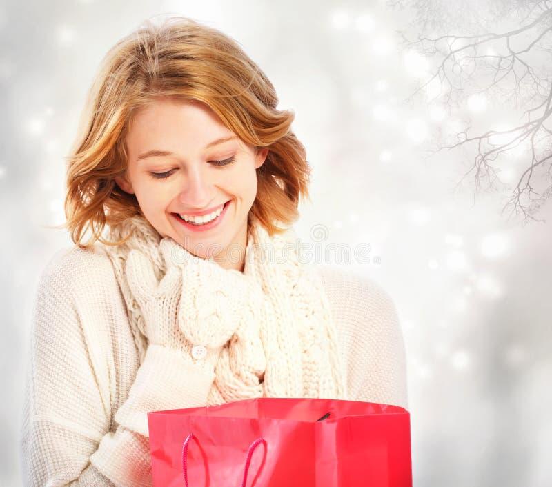 Härlig ung kvinna som ser en gåvapåse royaltyfria foton