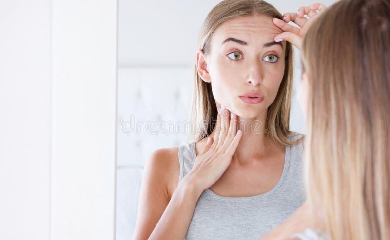 Härlig ung kvinna som ser i en spegel och trycker på hennes framsida royaltyfria bilder