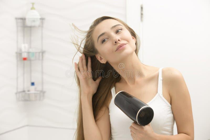 Härlig ung kvinna som ser spegeluttorkninghåret royaltyfria foton
