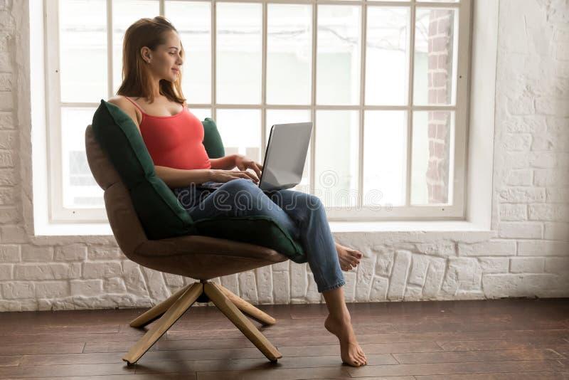 Härlig ung kvinna som sitter i bekväm stol och använder bärbara datorn fotografering för bildbyråer