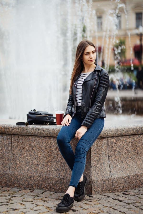 Härlig ung kvinna som sitter nära springbrunnen på gatan, stads- stil arkivfoto