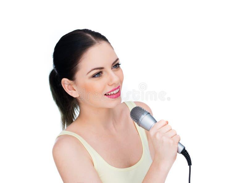 Härlig ung kvinna som sjunger in i en mikrofon royaltyfri foto