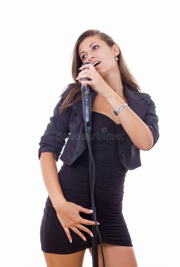 Härlig ung kvinna som sjunger på mikrofonen i svart klänning arkivbilder