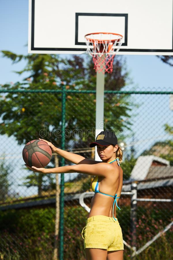 Härlig ung kvinna som spelar basket utomhus royaltyfri foto