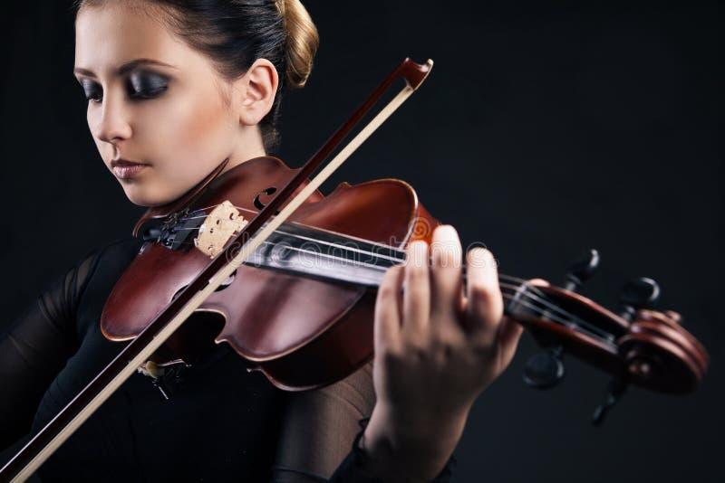 Härlig ung kvinna som spelar fiolen över svart arkivfoto