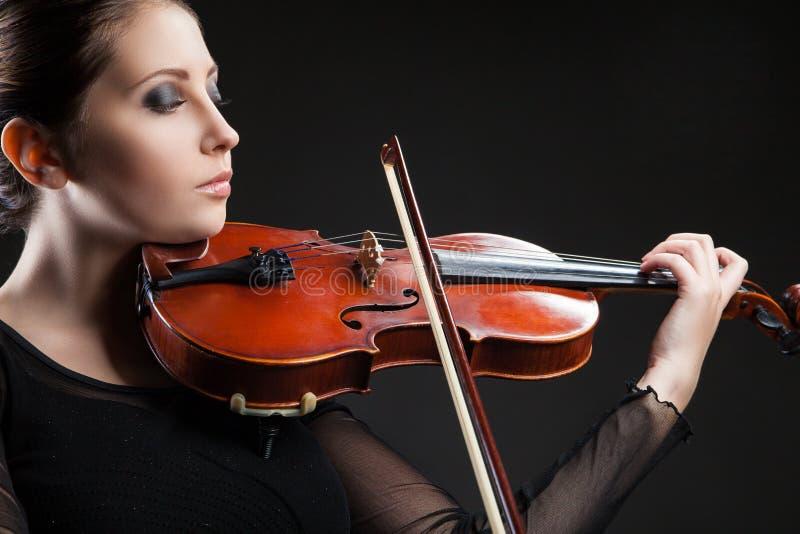 Härlig ung kvinna som spelar fiolen över svart arkivbild