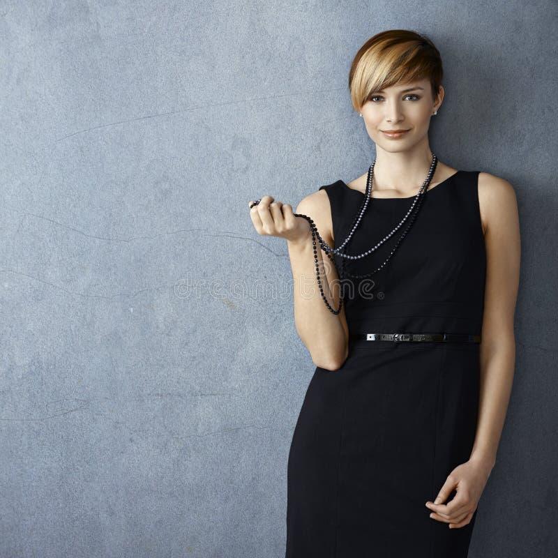 Härlig ung kvinna som spelar med den pärlemorfärg halsbandet arkivbild