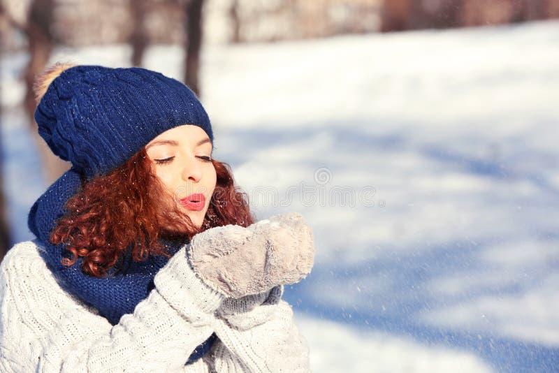 Härlig ung kvinna som spelar med snö utomhus arkivbilder