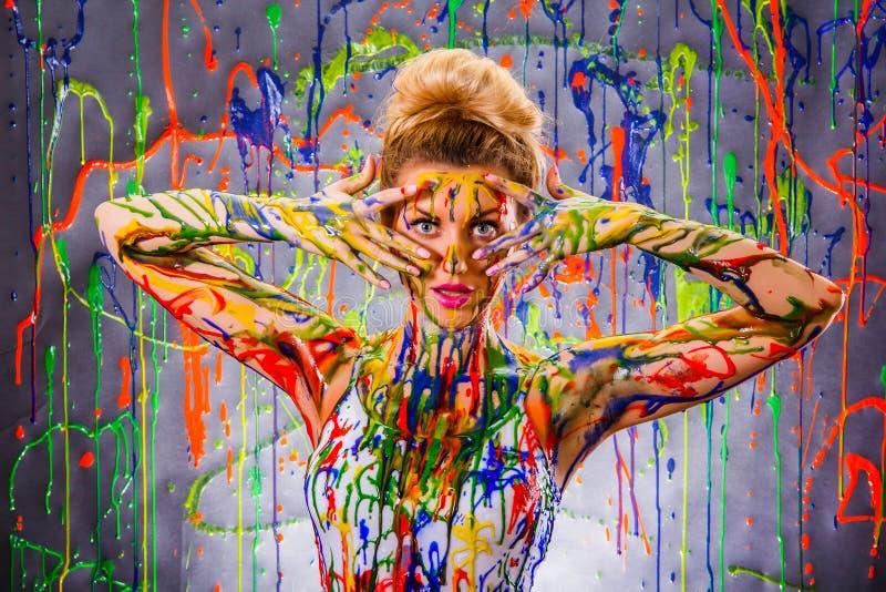 Härlig ung kvinna som täckas med målarfärger arkivbilder