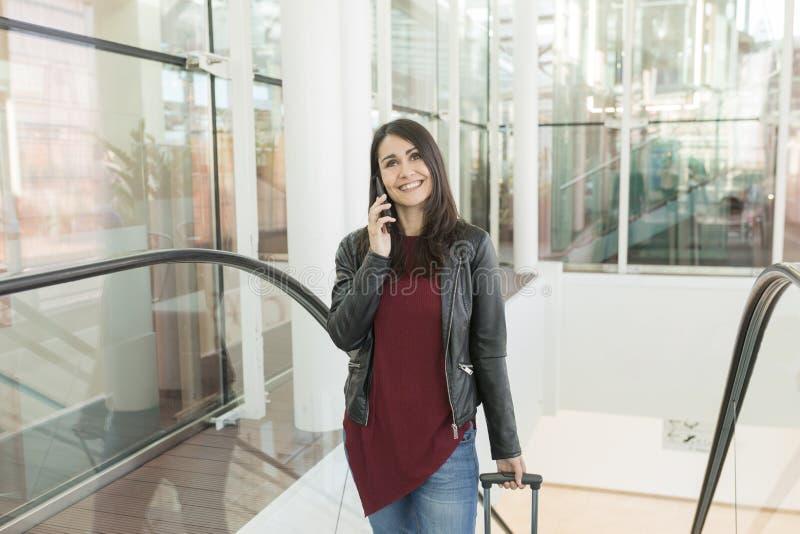 Härlig ung kvinna som talar på hennes mobiltelefon och le Loppbegreppet på flygplatsen, går hon upp trappa med a royaltyfria bilder