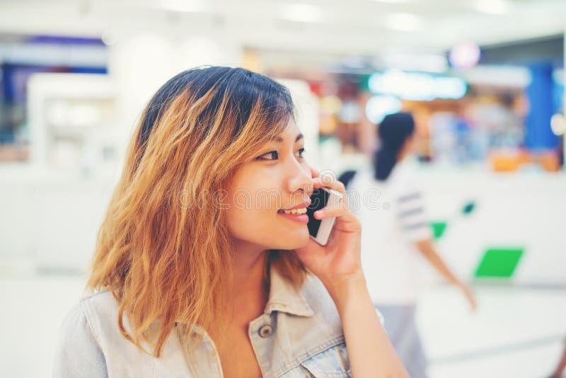 Härlig ung kvinna som talar på telefonen i shoppinggallerian fotografering för bildbyråer