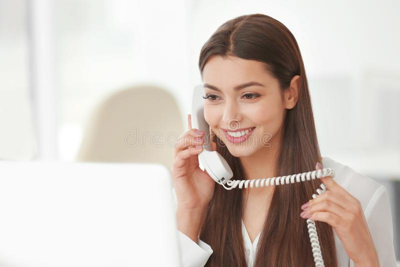 Härlig ung kvinna som talar vid telefonen, medan arbeta med datoren i regeringsställning arkivbilder
