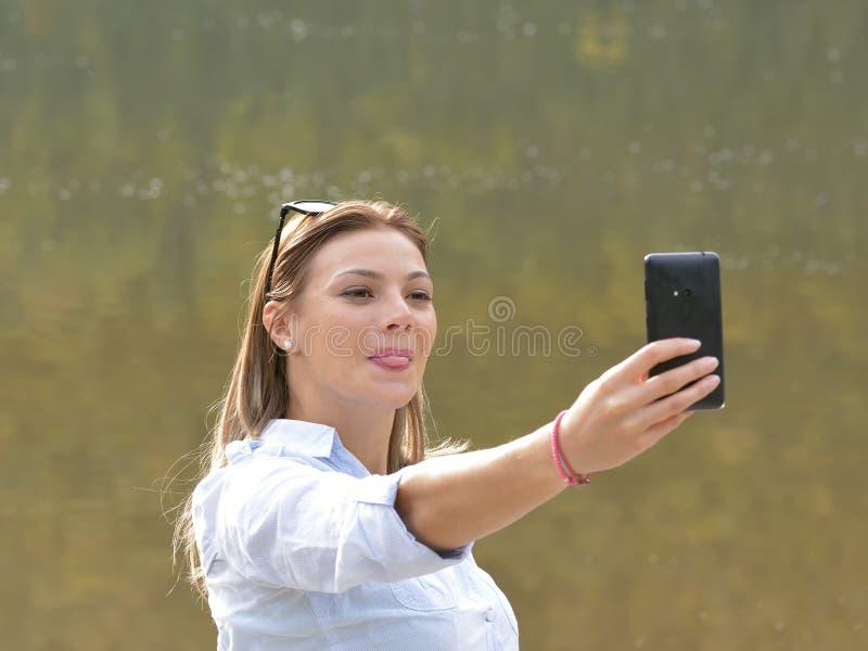 Härlig ung kvinna som tar en selfie i natur arkivbild