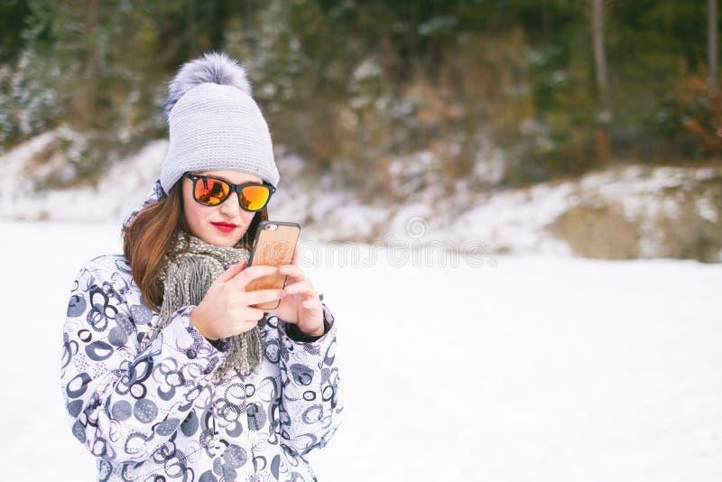 Härlig ung kvinna som tar en selfie i vinternatur Nätt kvinna som tar ett foto i en natur vinter för blåa snowflakes för bakgrund arkivfoton