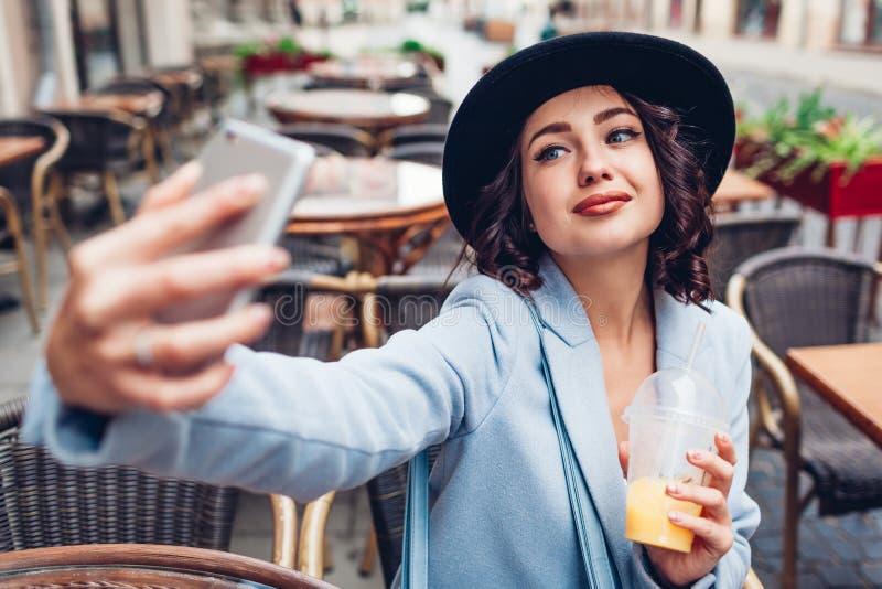 Härlig ung kvinna som tar selfie, medan ha orange fruktsaft i utomhus- kafé arkivfoton