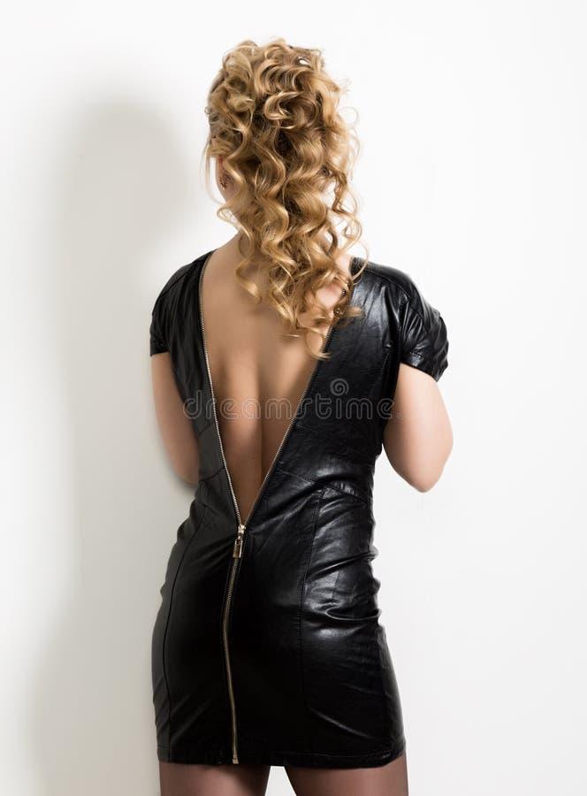 Härlig ung kvinna som tvärt bär lädersvartklänningen med naken baksida på en ljus bakgrund arkivfoto