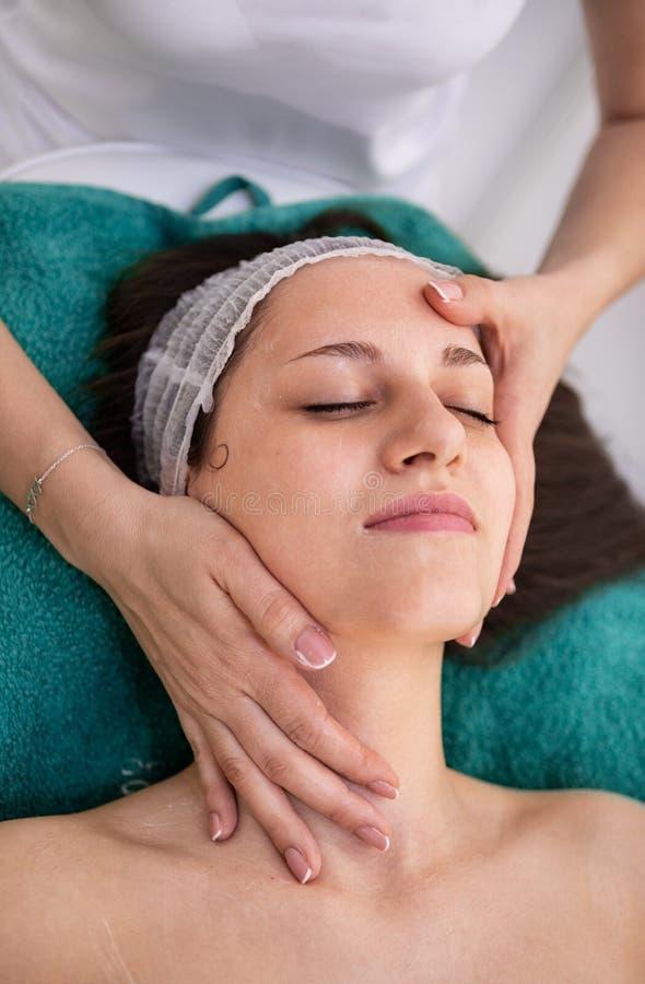 Härlig ung kvinna som tycker om i ansikts- massage fotografering för bildbyråer