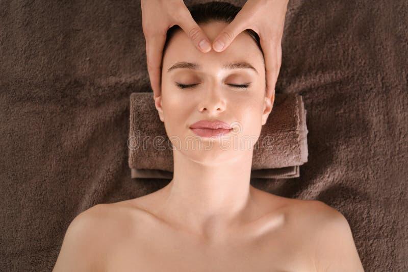 Härlig ung kvinna som tycker om massage i brunnsortsalong arkivfoton