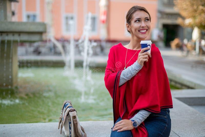 Härlig ung kvinna som utanför vilar på en brunn, medan dricka kaffe royaltyfri bild