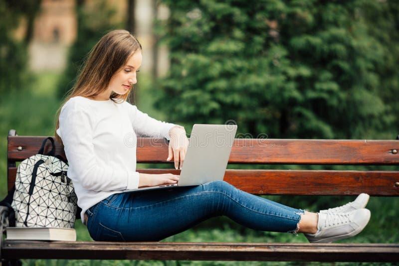 Härlig ung kvinna som utomhus lägger på bänk och arbete på bärbara datorn royaltyfri bild