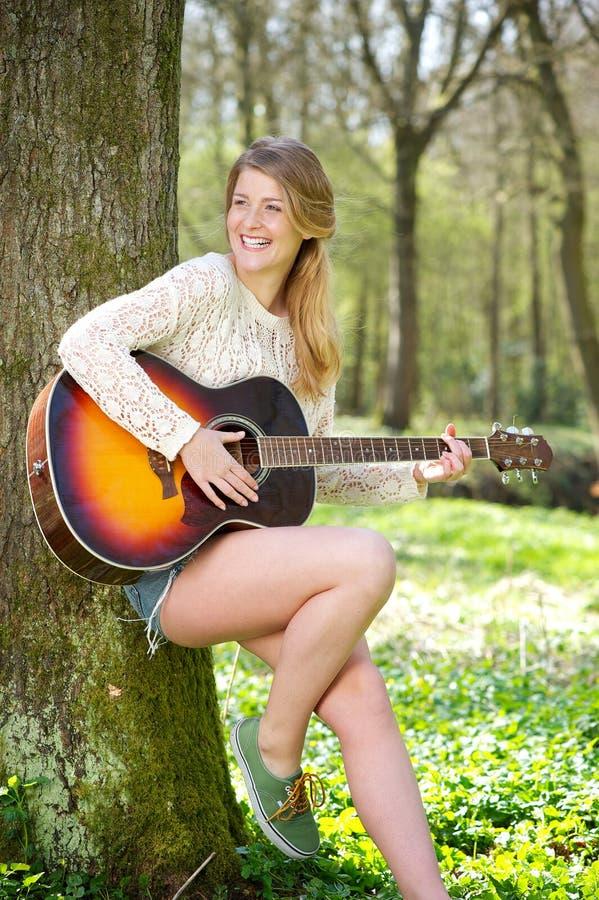 Härlig ung kvinna som utomhus ler med gitarren arkivfoton