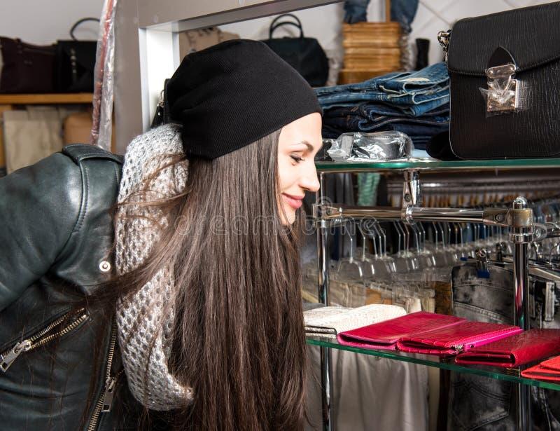 Härlig ung kvinna som väljer läderhandväskan royaltyfria bilder