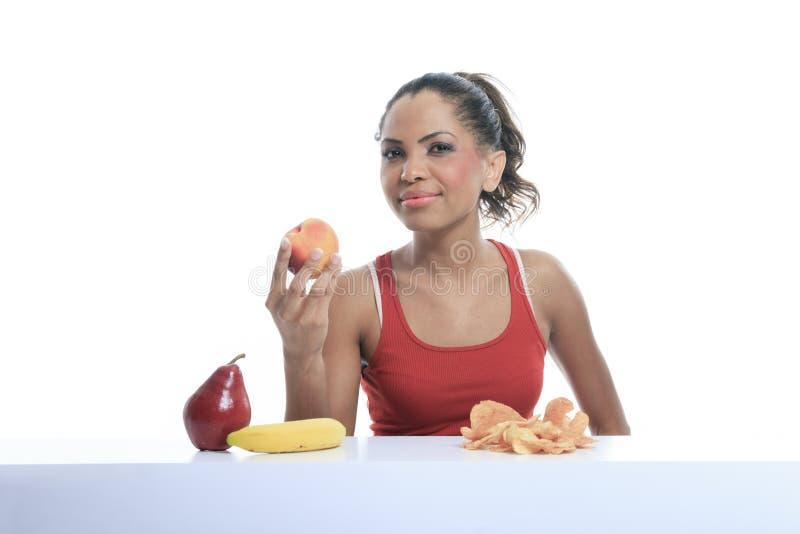 Härlig ung kvinna som väljer mellan frukter och arkivfoton