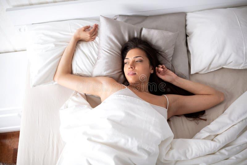 Härlig ung kvinna som vaknar upp att koppla av i hennes säng royaltyfri foto